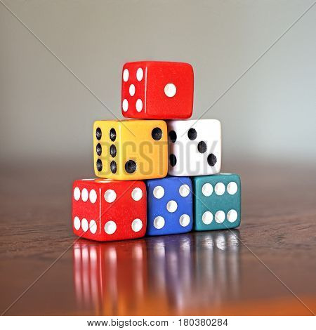 Tower of six colored dice with numbers from 1 to 6 on a wooden game table soft background