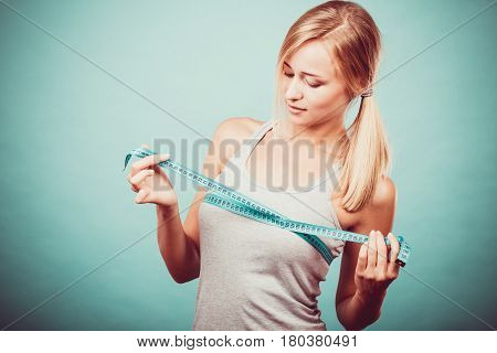 Fitness woman fit girl in sportswear with measure tape measuring her size chest breast on blue
