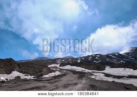 dirt road to summit craters of Mount Etna that emitting white smoke, Sicily