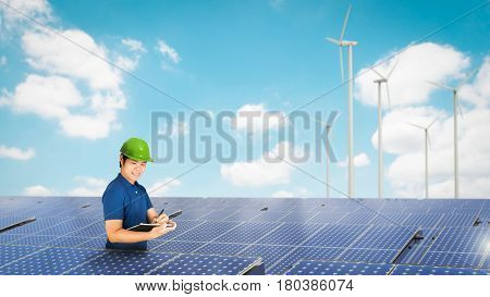 solar panel technician with solar panel and wind turbines