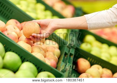 sale, shopping, food, consumerism and people concept - hand with apples at grocery store