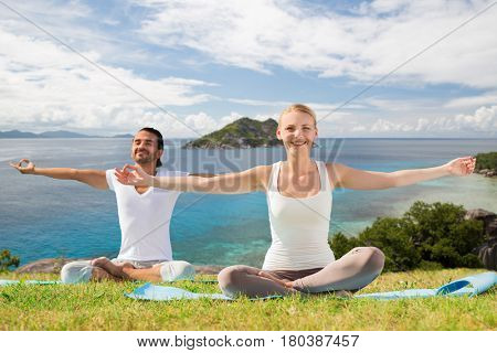 fitness, sport and people concept - happy couple making yoga exercises outdoors