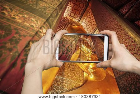 Tourist using smartphone taking a photo of the statue of the Reclining Buddha at Wat Pho, temple in Thailand