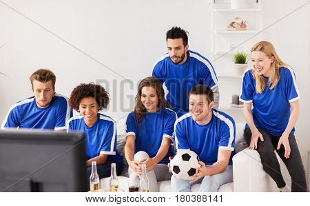 friendship, leisure, sport and entertainment concept - happy friends or football fans with ball watching soccer on tv at home