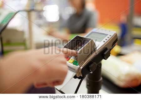 shopping, sale, consumerism and people concept - hand entering pin code at grocery store or supermarket cash register