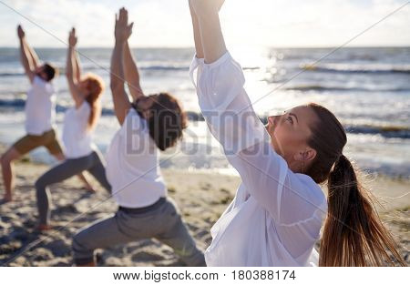 fitness, sport, yoga and healthy lifestyle concept - group of people making high lunge or crescent pose on beach