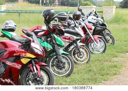Row Of Colourful Parked Motorbikes On Green Grass
