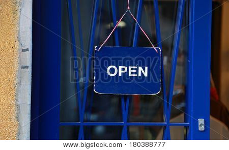 A view of the blue open signboard hung on the doo