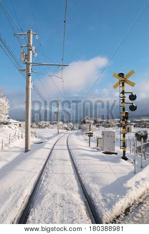 Railway track for local train with white snow fall in Japan