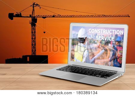 Laptop showing construction service concept for engineer with foreman worker checking construction site for new Infrastructure construction project