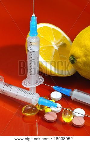 Lemons on a red background with syringes and pills. Medical preparations and vitamin C. Subcutaneous injectors with tablets side by side with lemons on a red background
