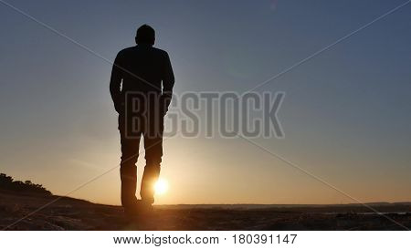 freedom. Man stands on a cliff sunset silhouette hand in sides lifestyle