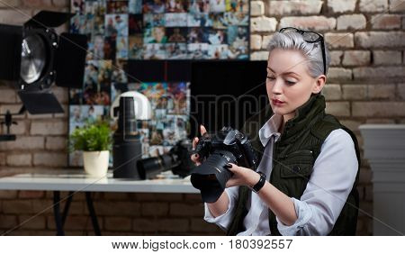 Young female photographer working in studio.