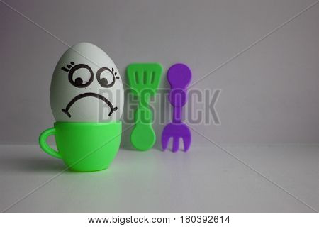 Egg with face. Concept of diet. Unsuccessful diet. Photo for your design