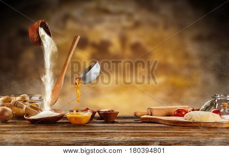 Dough preparation, baking ingredients placed on wooden table, ready for cooking. Copyspace for text. Flying food in motion