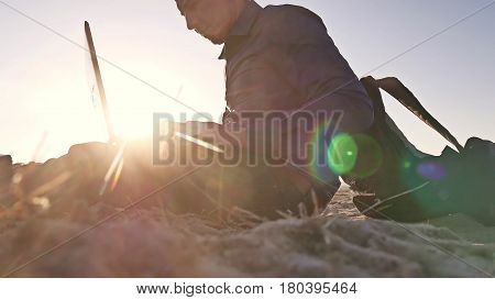 Freelancer. Man working on laptop freelancer sitting on the sand sunset sun glare sun silhouette