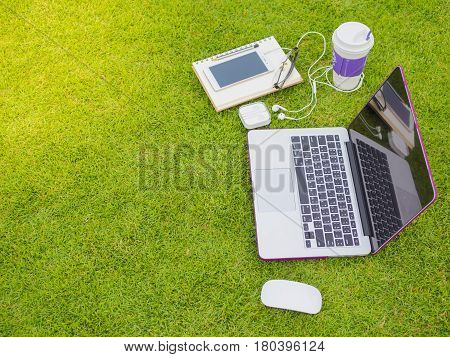 Laptop notebook smart phone and stack of old tattered book on the green grass