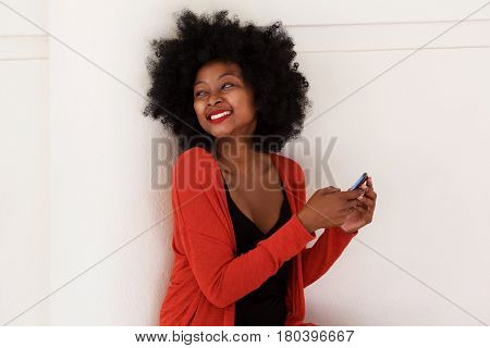 Happy Black Woman With Smart Phone By White Wall