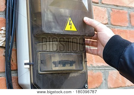 Close up of male hand touching electrical board hanging on red brick wall