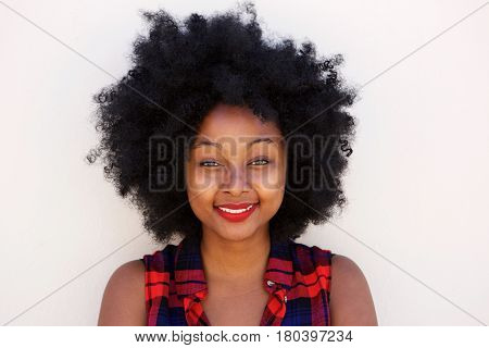 Happy Young Black Woman With Afro Hairstyle By White Wall