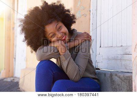 Happy Young Woman Sitting On Steps Leaning Head On Arms