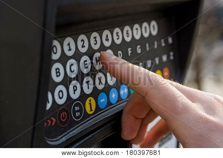 Close up of male hand pressing buttons on parking meter with colorful buttons in the street