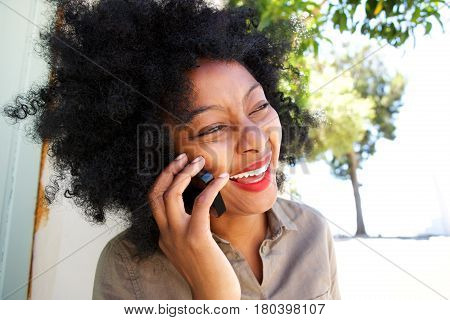 African Woman Laughing With Mobile Phone Outside