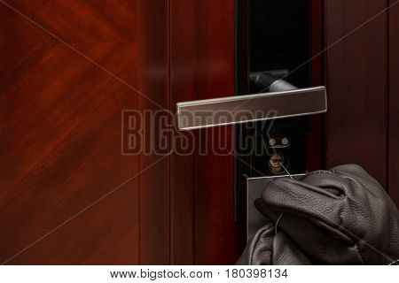 thief opening a door lock by steel wire