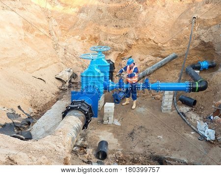 Worker In Safety Clothes Drive Valve Conduit  On City Potable Water Pipe