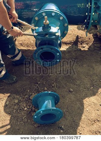 Worker Hands Screwing  Nuts On New Dring Water Piping.