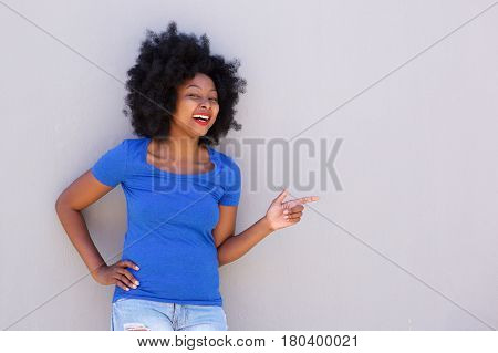 Fashionable Young Woman Smiling And Pointing To Wall