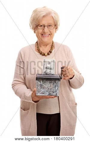 Elderly woman destroying a dollar banknote in a paper shredder isolated on white background