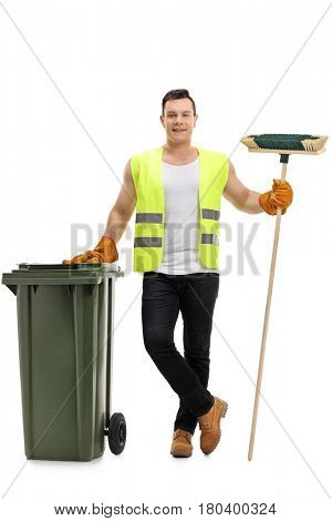 Full length portrait of a waste collector with a broom and a garbage bin isolated on white background