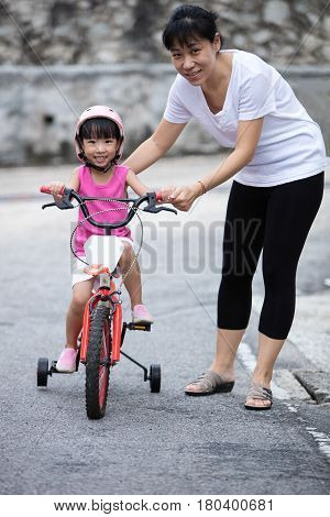 Asian Chinese Little Girl Riding Bicycle With Mom Guide