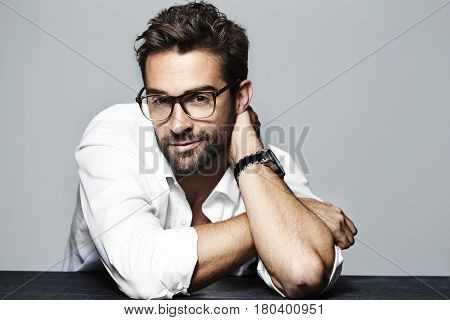 Spectacled and handsome in studio portrait Flirty