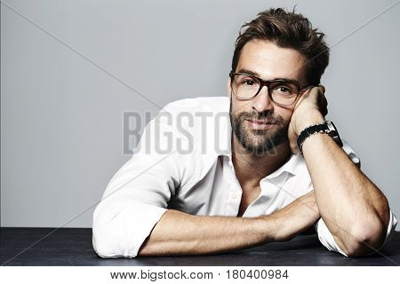 Handsome and spectacled man leaning in studio