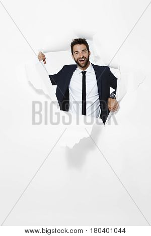 Braking Businessman emerging from paper portrait studio