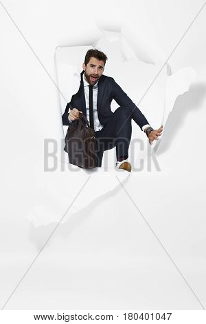 Businessman escaping from torn paper portrait studio