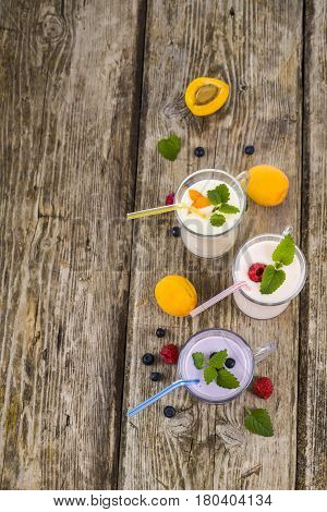 Three Glasses With Smoothies  Or Yogurt With Fresh Berries On A Wooden Table.