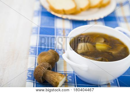 Soup Of Wild Mushrooms On A Wooden Table.