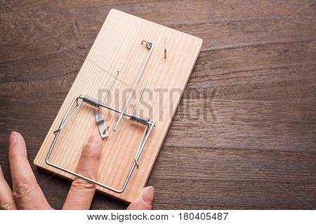 Finger caught by the mousetrap device on wooden table