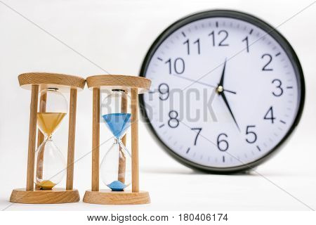 Two sand glasses on white background in front of wall clock