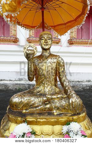 Smile buddha statue at public temple in Thailand