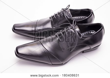 Sideways black leather shoes on a white background