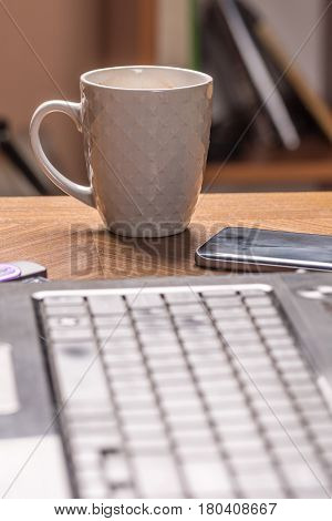 Cup Of Coffee On The Table With Blurred Lap Top