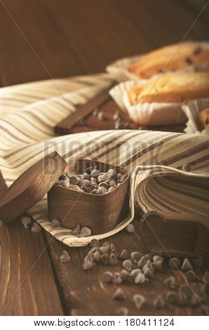 Low key close-up still life with cupcake and chocolate drops in small wooden box on napkin on wooden plank