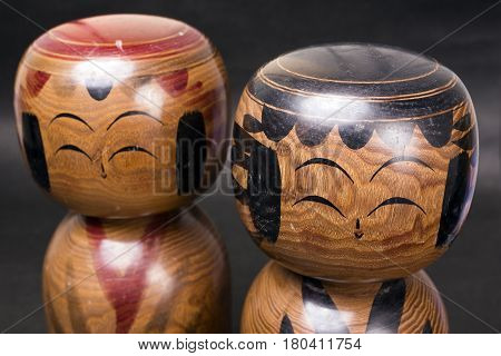 Meoto Kokeshi(Japanese couple of limbless wooden doll) in front of dark background