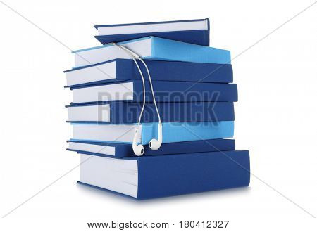 Audiobook concept. Stack of books and earphones on white background