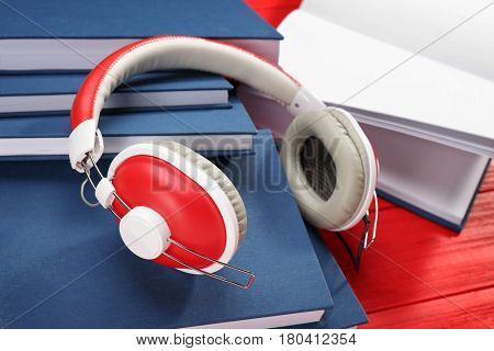 Audiobook concept. Hardcover books and headphones on wooden background, closeup