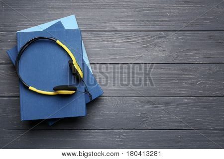 Audiobook concept. Stack of books and headphones on wooden background